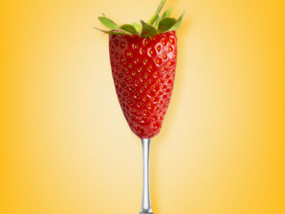 A strawberry in the shape of a champagne flute that on a yellow background that reads