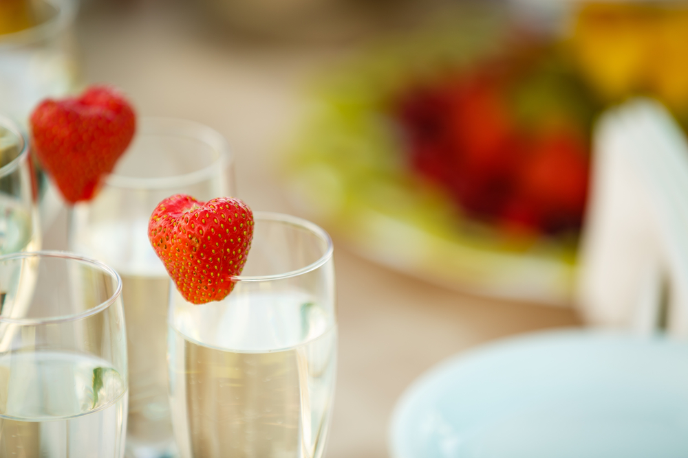 Champagne flutes with strawberries resting on the rim
