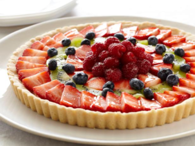 A large fresh fruit tart on a plate