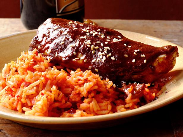 A Meican burrito covered in mole sauce with a side of rice