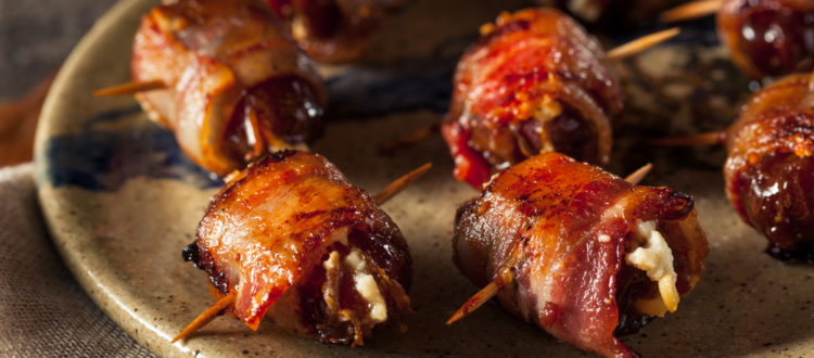 a plate of bacon wrapped date appetizers
