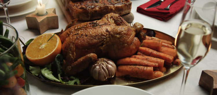 A table with a plate of roasted whole chicken and vegetables
