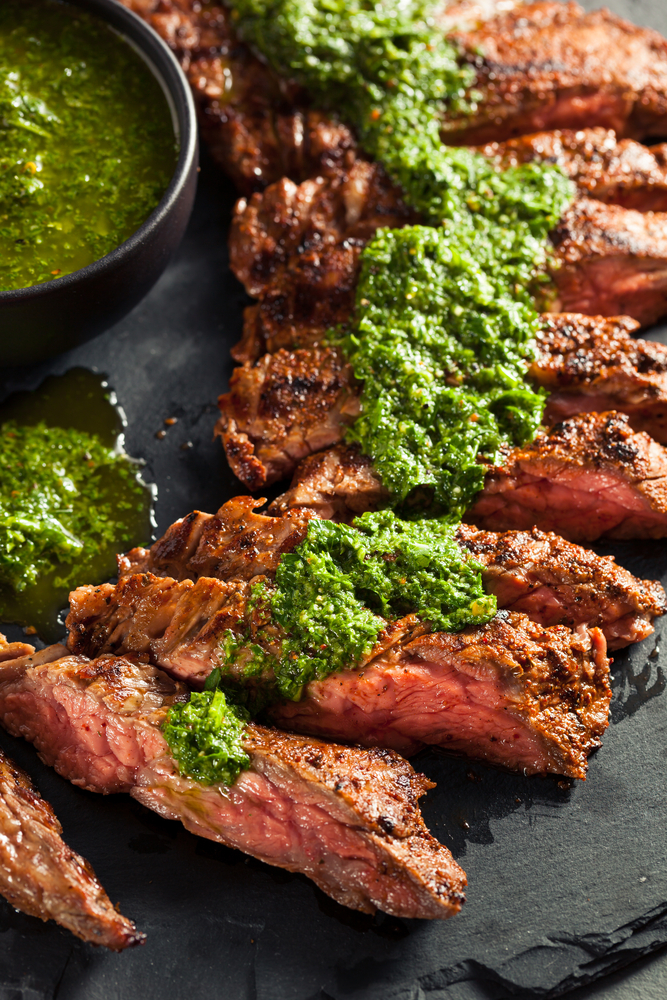 Plate of sliced steak with chimichurri sauce