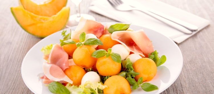A cantaloupe, proscuitto, and mozzarella salad paired with champagne
