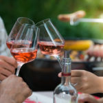 Three wine glasses making a toast at a barbecue